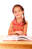 Smiling little girl reading book on the desk Royalty Free Stock Photos