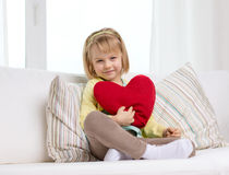 Smiling little girl with red heart at home Royalty Free Stock Image