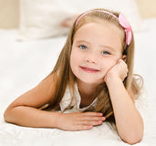 Smiling little girl resting on the bed Stock Photo