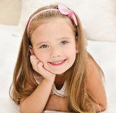 Smiling little girl resting on the bed Stock Images