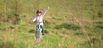 Smiling little girl riding a bike Royalty Free Stock Photography