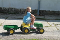 Smiling little girl riding a tractor Stock Images