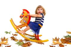 A smiling little girl riding a wooden horse Royalty Free Stock Image