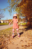 Smiling little girl roller skating in autumn park Royalty Free Stock Photo