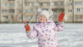 Smiling little girl running outdoors on snowy stadium near school