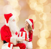 Smiling little girl with santa claus and gifts Royalty Free Stock Photos
