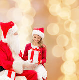 Smiling little girl with santa claus and gifts Royalty Free Stock Photography