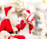 Smiling little girl with santa claus and gifts Royalty Free Stock Photo