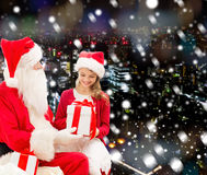 Smiling little girl with santa claus and gifts Stock Photography