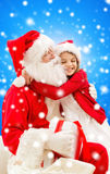 Smiling little girl with santa claus Stock Images