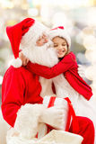 Smiling little girl with santa claus Stock Photos