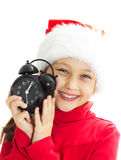 Smiling little girl in a Santa hat is holding alar Stock Image