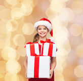 Smiling little girl in santa helper hat with gifts Royalty Free Stock Photos