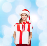 Smiling little girl in santa helper hat with gifts Royalty Free Stock Photography