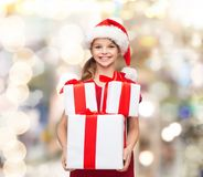 Smiling little girl in santa helper hat with gifts Stock Photography