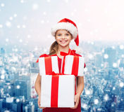 Smiling little girl in santa helper hat with gifts Stock Images