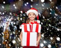 Smiling little girl in santa helper hat with gifts Stock Image