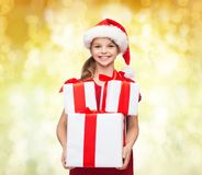 Smiling little girl in santa helper hat with gifts Stock Photos
