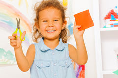 Smiling little girl with scissors and square Royalty Free Stock Photos