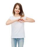 Smiling little girl showing heart with hands stock photo