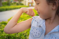 Smiling little girl showing her hand biceps muscles strength Royalty Free Stock Image