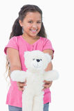 Smiling little girl showing her teddy bear to camera Royalty Free Stock Photography