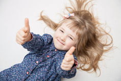 Smiling little girl showing thumb up Royalty Free Stock Image