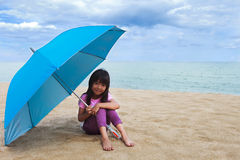 Smiling little girl sitting at beach Stock Photos