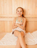 Smiling little girl sitting on bench at sauna Royalty Free Stock Image