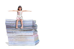 Smiling little girl sitting on a book Royalty Free Stock Image