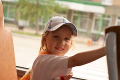 Smiling little girl sitting in a bus. In summer Royalty Free Stock Image