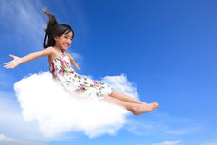 Little girl sitting on the cloud over sky Stock Photos