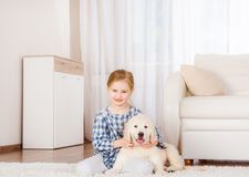 Smiling little girl sitting with retriever puppy. Smiling little girl sitting with cute fluffy retriever puppy at home royalty free stock photos