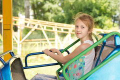 Smiling little girl sitting on a fairground ride Royalty Free Stock Images