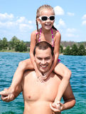 Smiling little girl sitting on father's shoulders Stock Photo