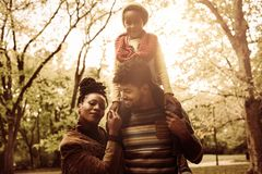Portrait of African American family in park together. Smiling little girl sitting on father shoulders. Family at park stock photography