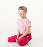 Smiling little girl sitting on the floor with closed eyes Royalty Free Stock Images
