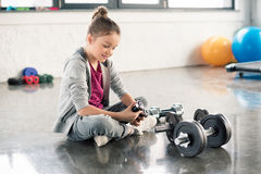 Smiling little girl sitting on floor and exercising with dumbbells in gym Royalty Free Stock Images