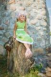 Smiling little girl sitting on large stump Stock Photo