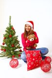 Smiling little girl sitting near a Christmas tree with a teddy b Stock Images