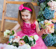 Smiling little girl  is sitting near the wooden stairs and color Royalty Free Stock Images