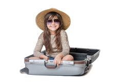 Smiling little girl sitting in the open suitcase royalty free stock photos