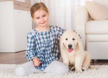 Smiling little girl sitting with retriever puppy. Smiling little girl sitting with cute fluffy retriever puppy at home stock images