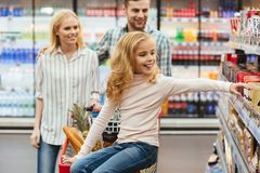 Smiling little girl sitting on a shopping cart. And choosing sweets with her parents at the supermarket Royalty Free Stock Image