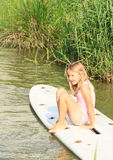 Smiling little girl sitting on surf board. Smiling little girl in pink swimsuite sitting on white surf board Royalty Free Stock Photo