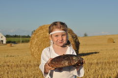 A smiling little girl in slavic traditional ornamented chemise holding a loaf of a rye bread in the harvested filed Royalty Free Stock Photos
