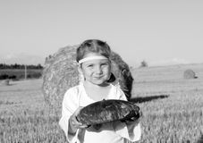 A smiling little girl in slavic traditional ornamented chemise holding a loaf of a rye bread in the harvested filed Stock Images