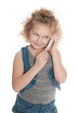 Smiling little girl speaks on a cell phone Royalty Free Stock Photos