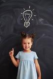 Smiling little girl standing against chalk drawing of light bulb Stock Photos
