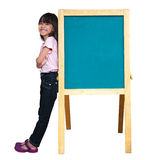 Smiling little girl standing beside a blackboard Royalty Free Stock Image
